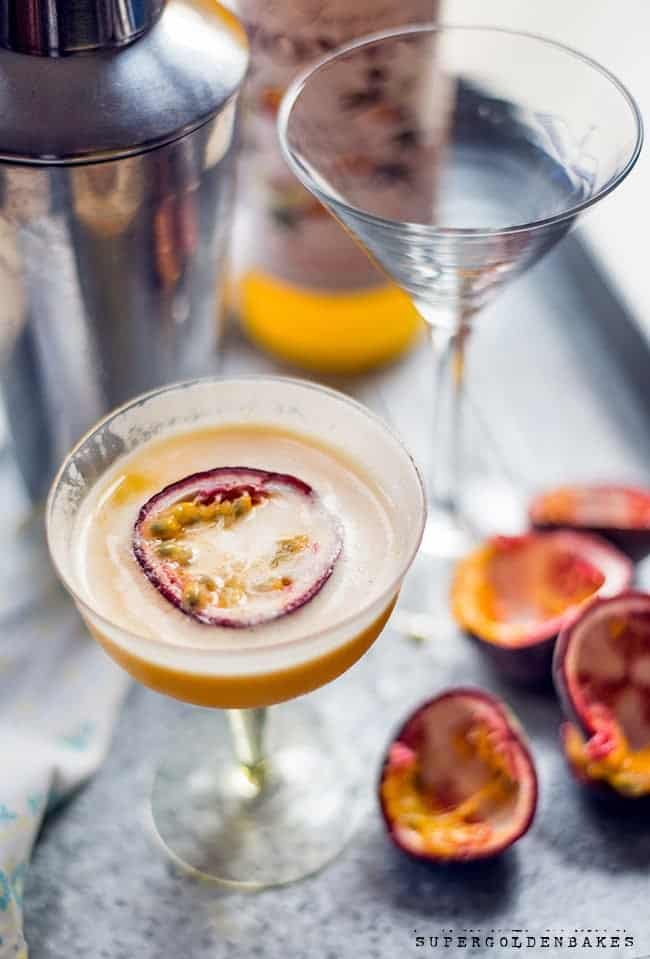 Passionfruit martini in a coupe glass on a metal tray with passion fruit on the side