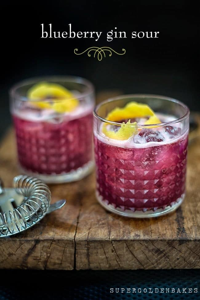 Blueberry gin sour in two rocks glasses garnished with lemon peel