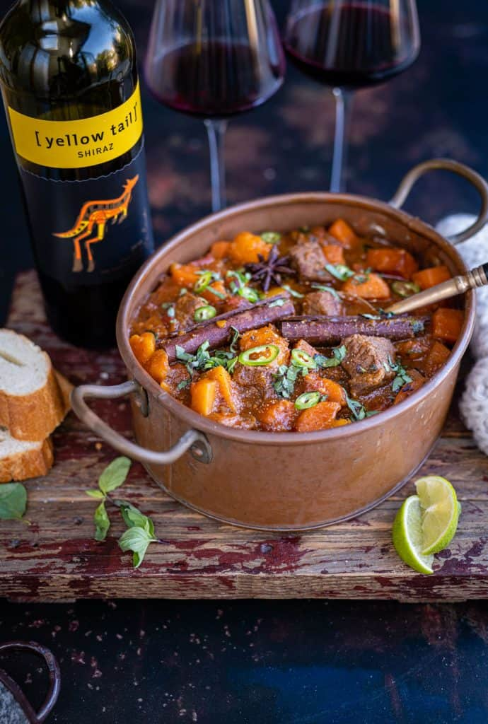 Pot of Vietnamese Beef stew with glasses of red wine