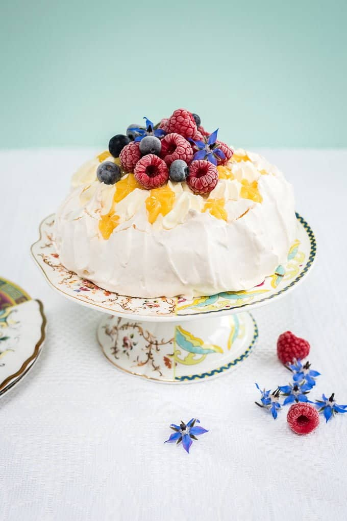 Pavlova with cream, lemon curd and fresh berries on a cake stand