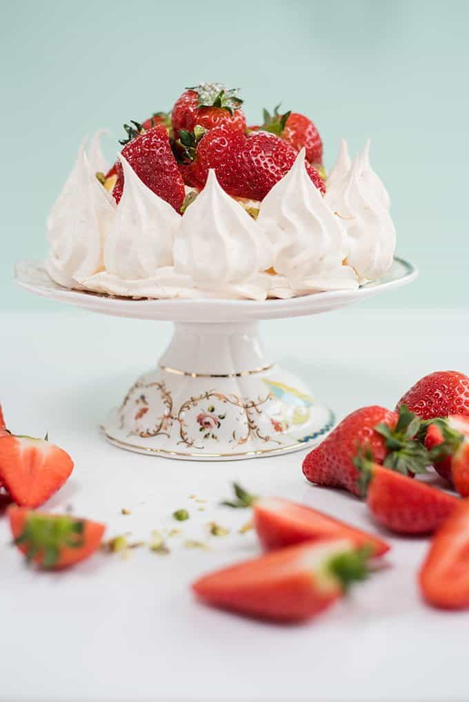 Pavlova crown with whipped cream, lemon curd and fresh strawberries
