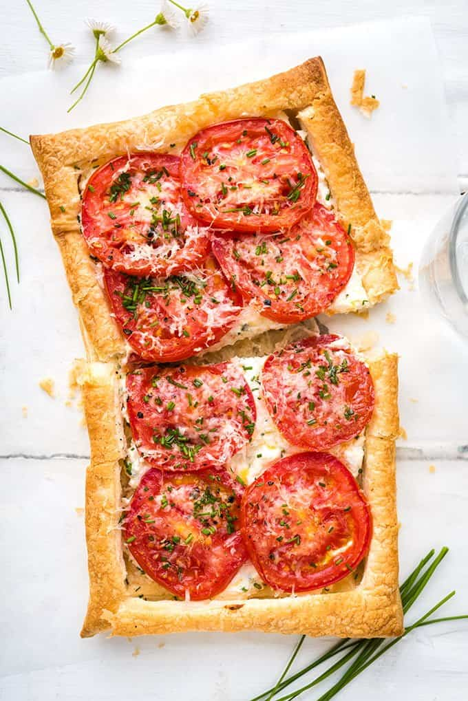 Close up on a roasted tomato tart made with puff pastry, ricotta and feta on white background