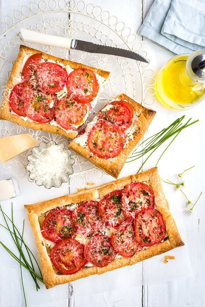 Two puff pastry tomato tarts on white background