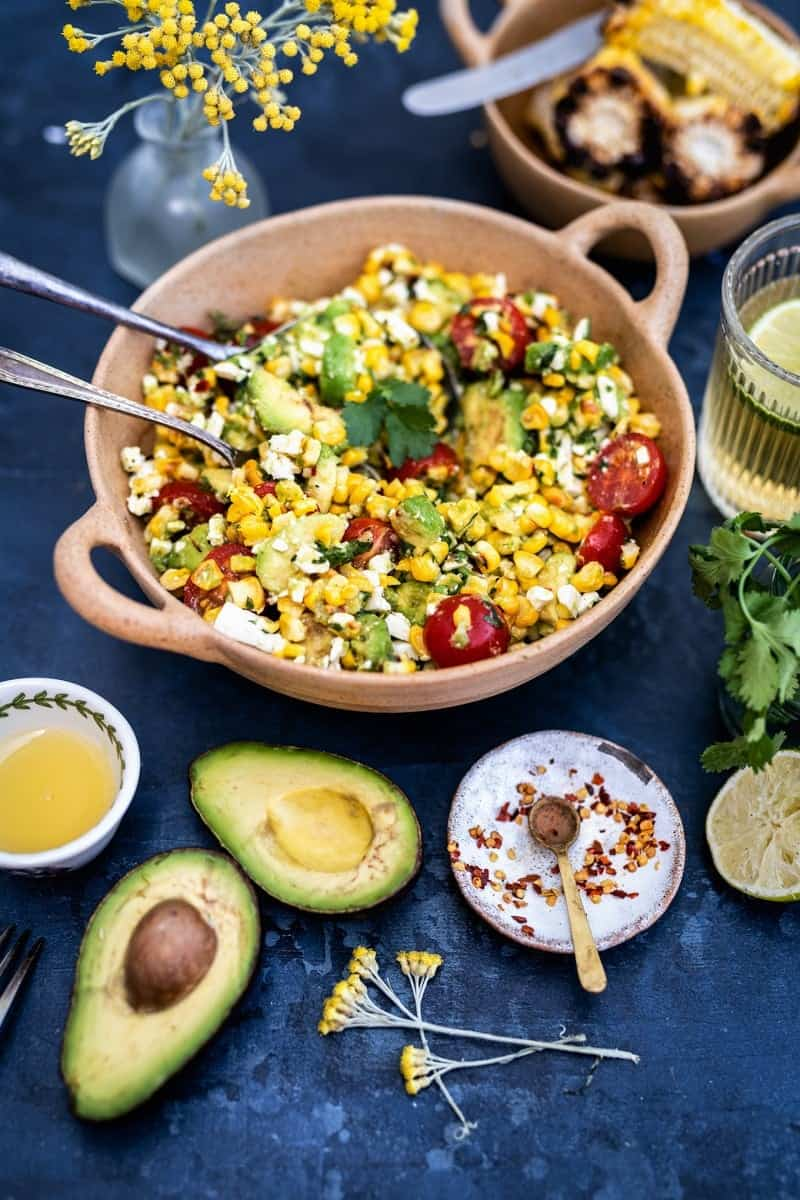 Grilled corn, feta and avocado salad with lime dressing in a bowl