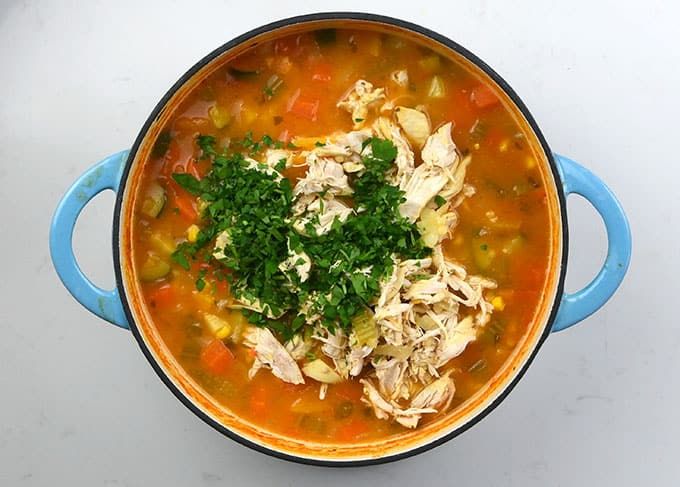 Adding vegetables and shredded chicken to soup
