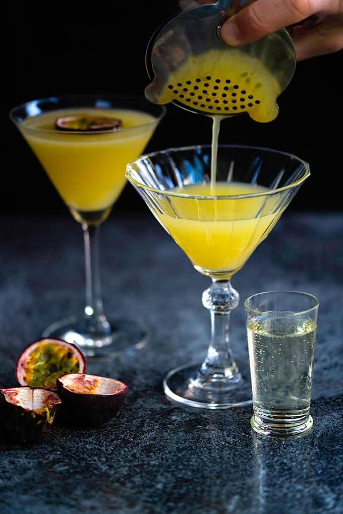 Pouring a passion fruit vodka martini into a cocktail glass