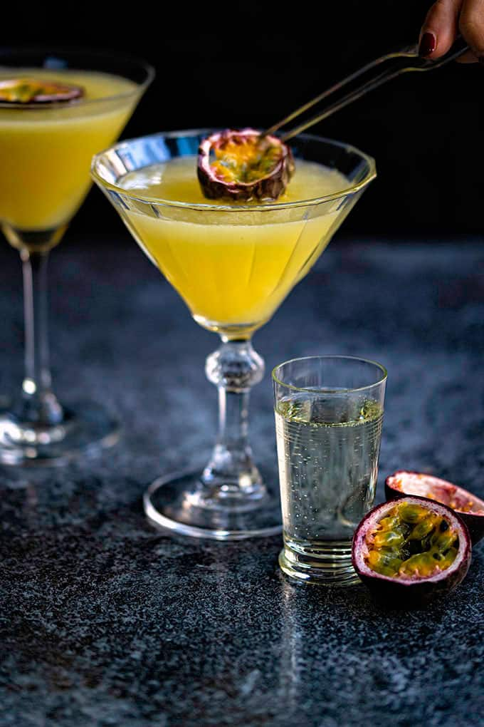 Adding a slice of passion fruit to a Porn Star Martini