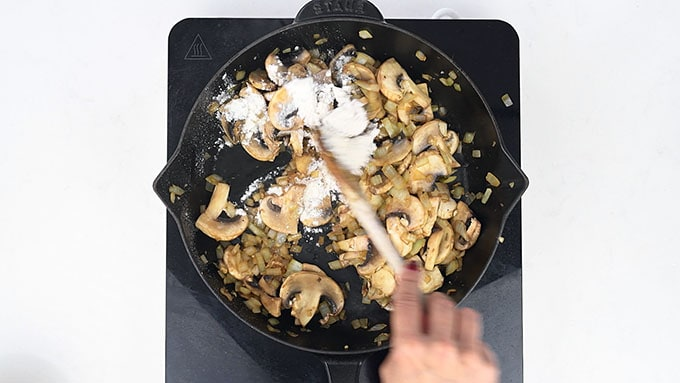 adding flour to onions and mushrooms in a skillet