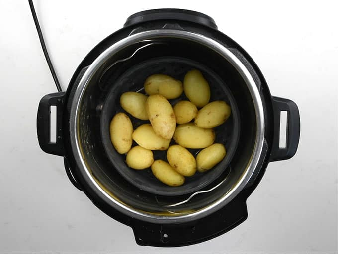 Baby potatoes placed in a steamer basket on top of a trivet in an Instant Pot