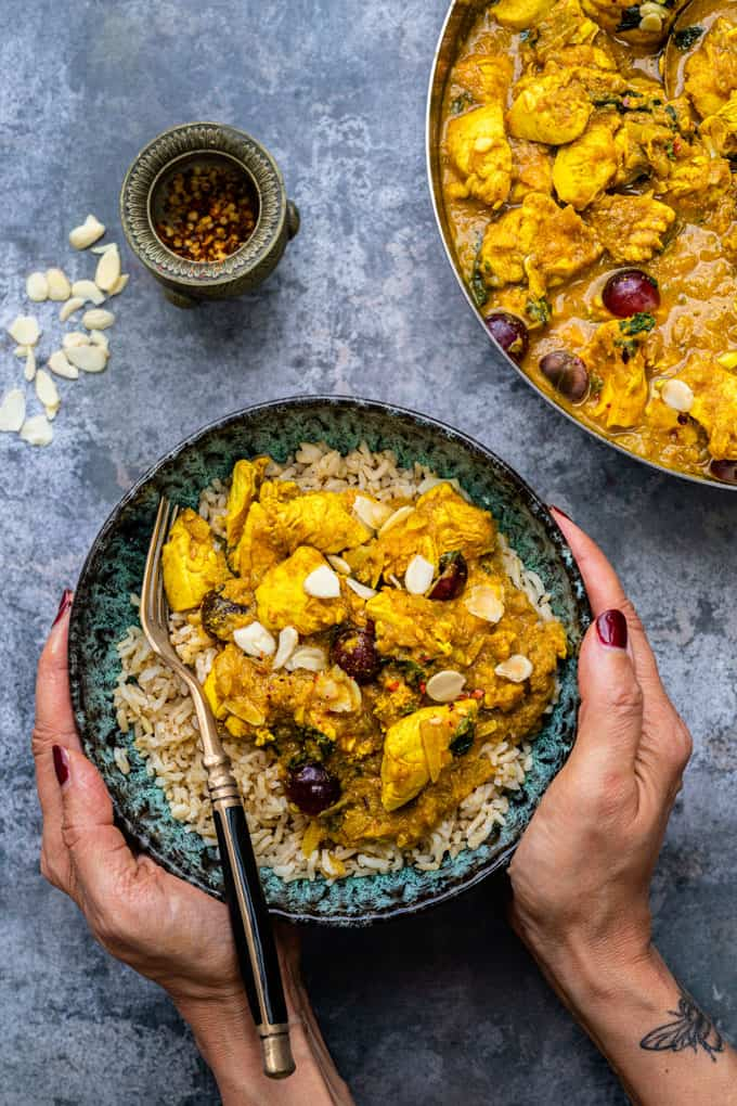 Chicken Korma served over brown rice in a bowl