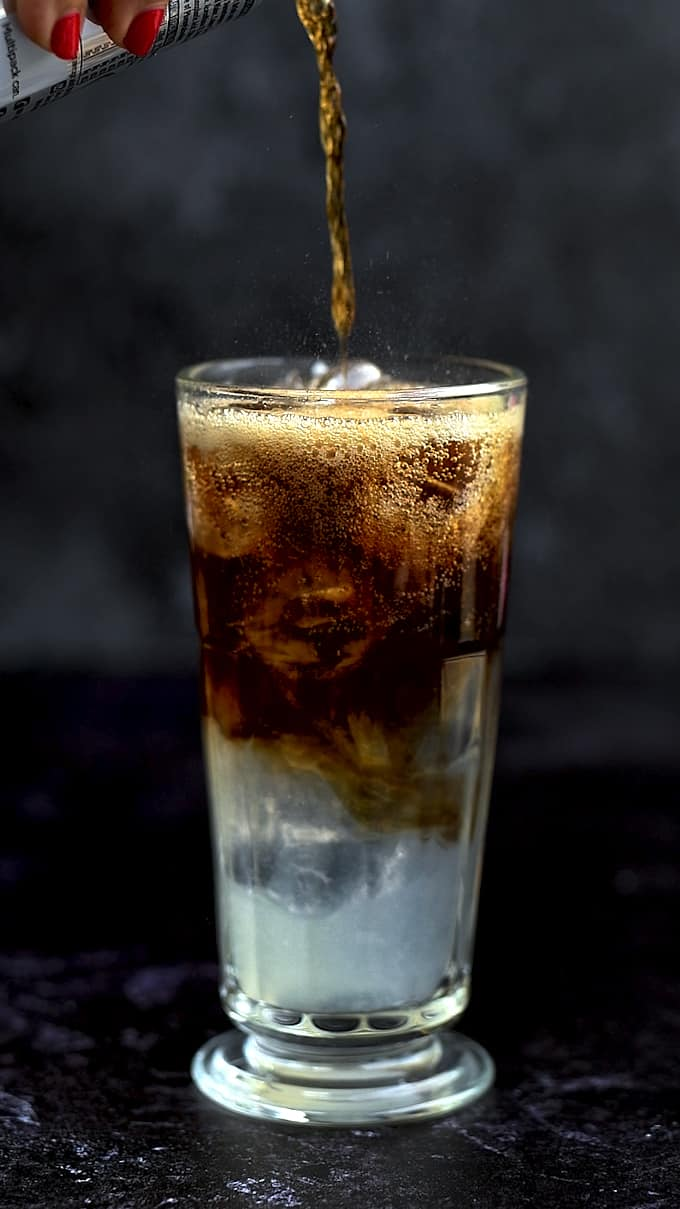 Topping a glass of Long Island drink with cola