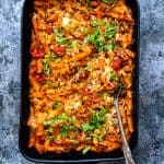 Slimming World pasta bake in a baking dish garnished with chopped basil