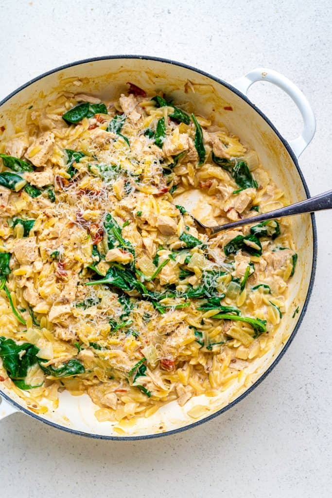 Orzo pasta with turkey, spinach and sun dried tomatoes in a cast iron casserole