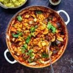 Vegetable curry in a large casserole dish with rice on the side