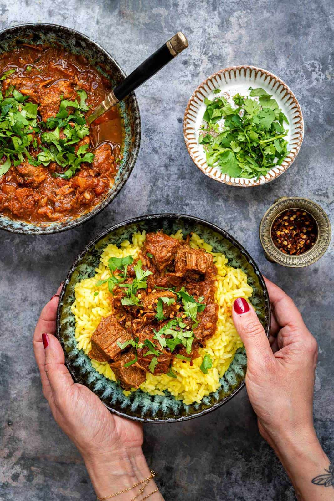 Bowl of beef curry served over rice garnished with chopped coriander