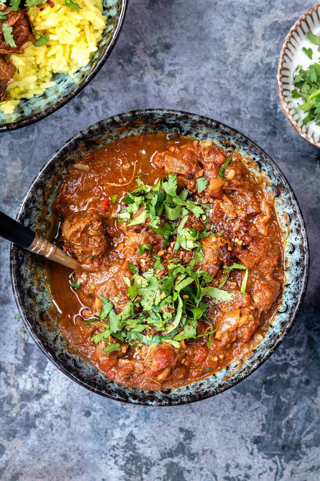 Bowl of tomato-based beef curry garnished with chopped coriander