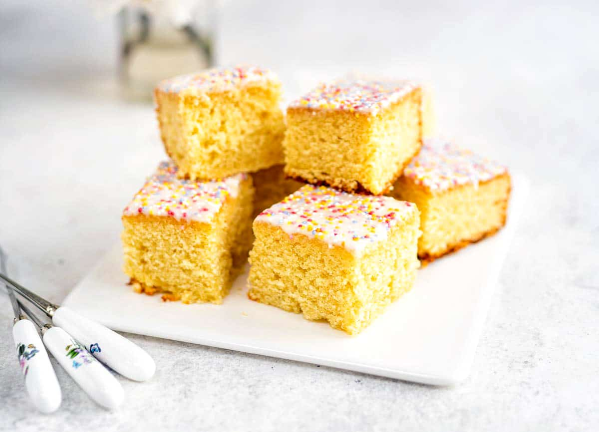 vanilla sheet cake cut into squares piled on a ceramic plate