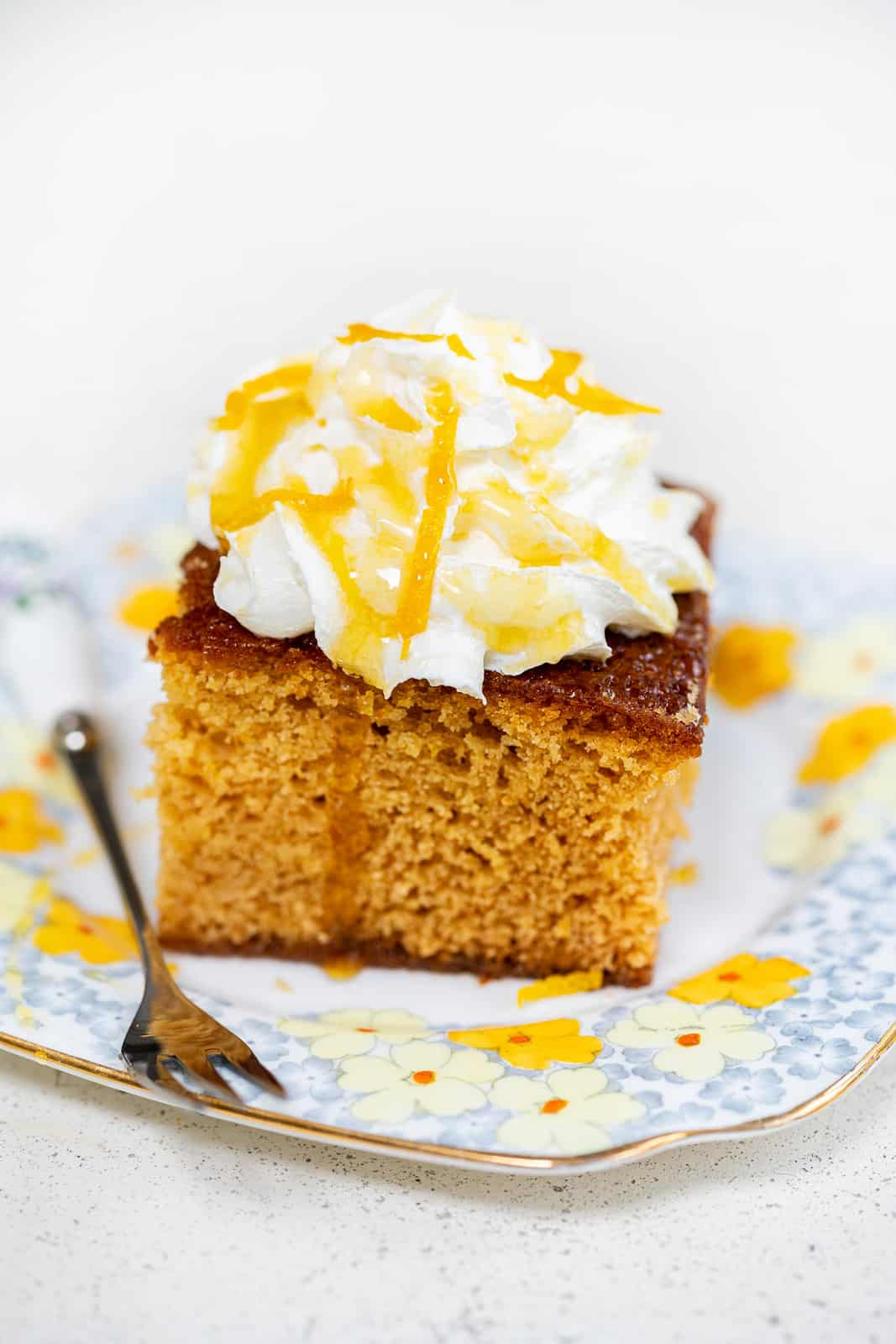 Golden syrup cake topped with whipped cream on a floral plate