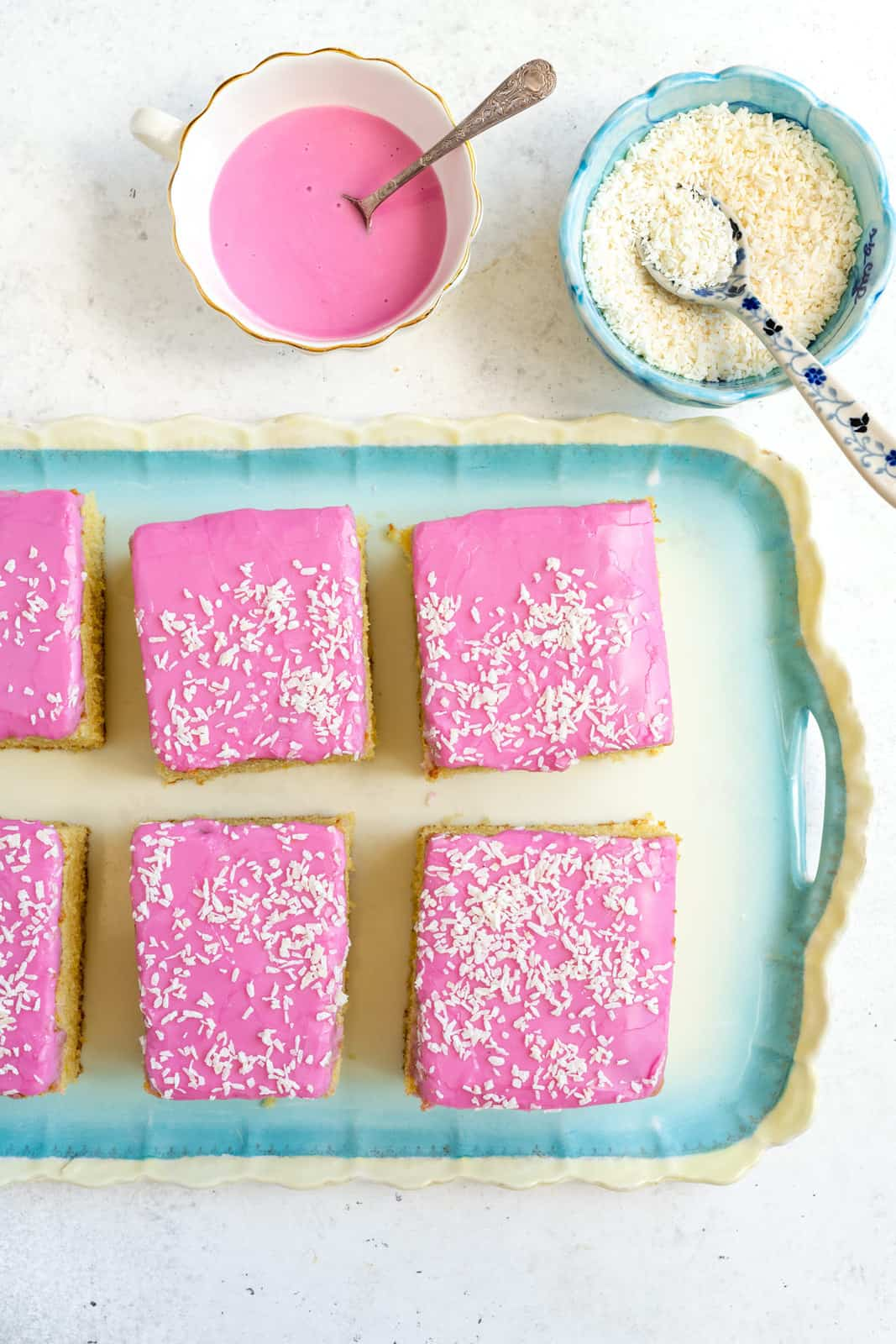 Tottenham cake sliced in squares on a tray with pink icing and coconut on the side
