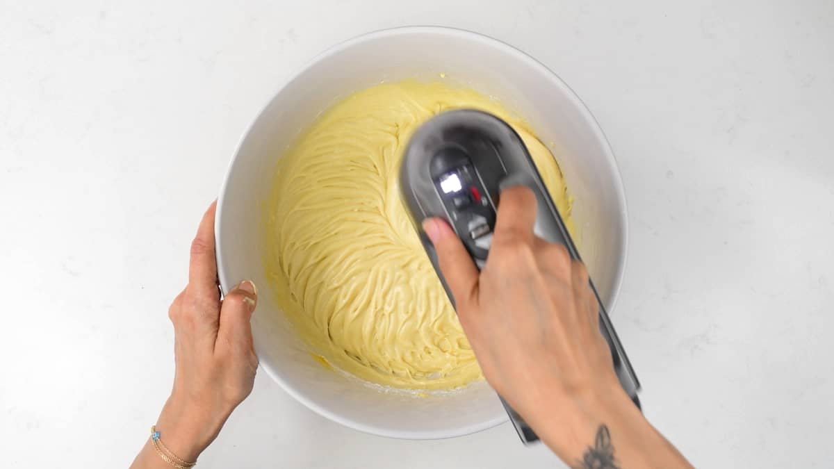 beating cake batter in a mixing bowl with a stand mixer
