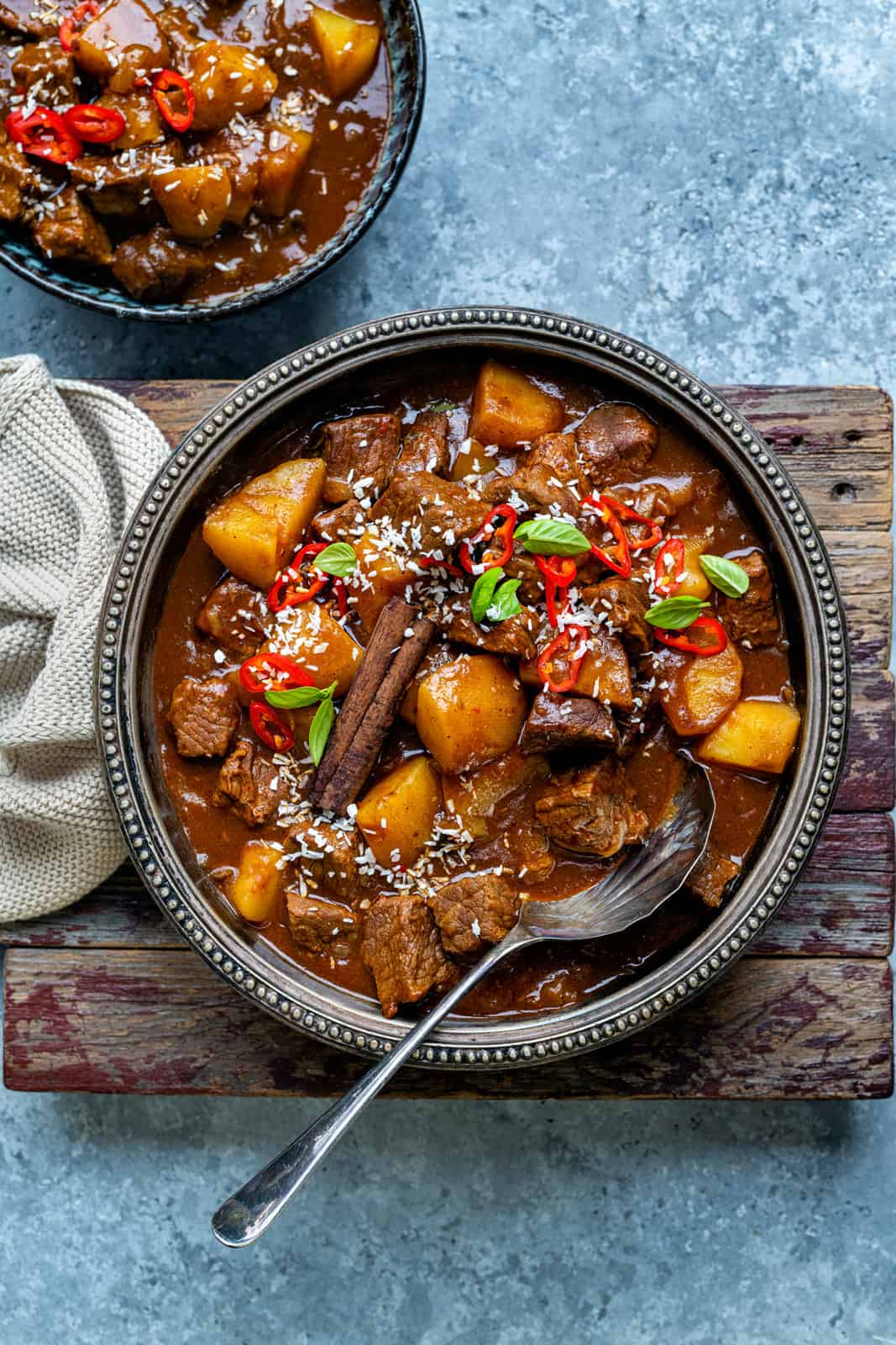 Coconut Beef Curry with potatoes served in a bowl garnished with basil and chopped chillies