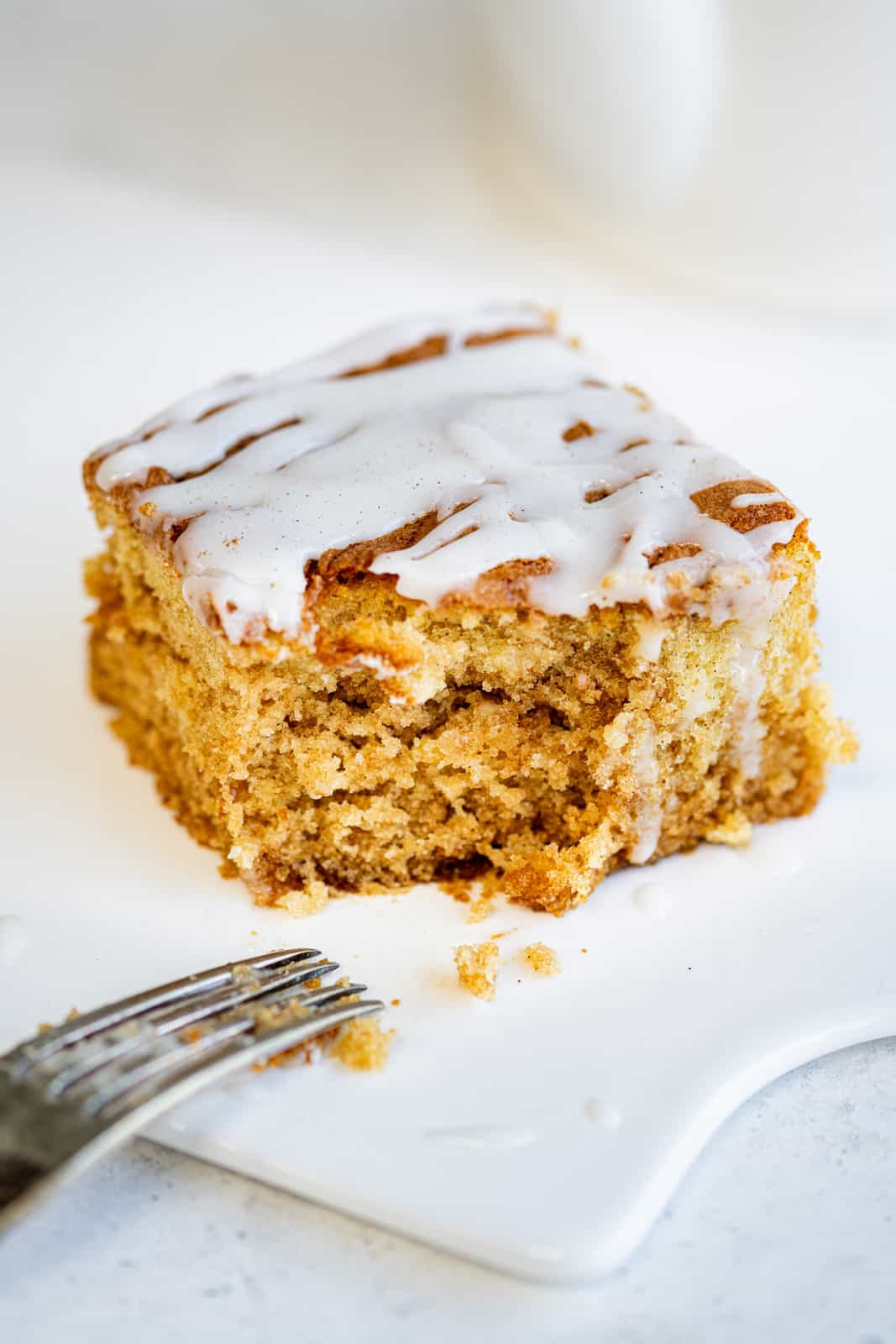 Slice of Cinnamon Roll cake with bite taken out