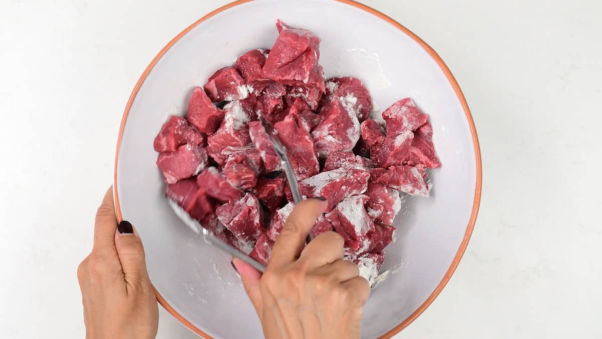 tossing beef cubes with flour in a large bowl