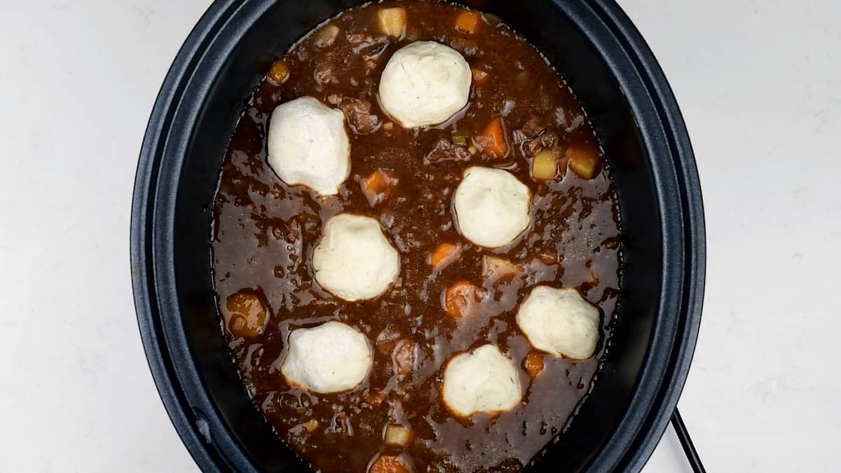 placing herb dumplings on to of beef stew in a slow cooker