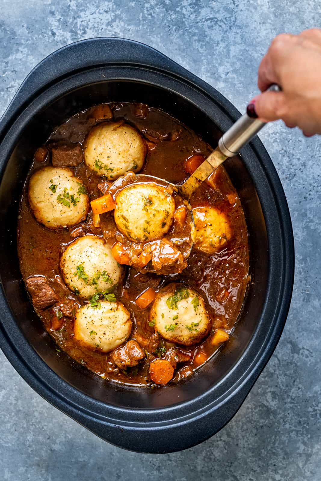 Beef stew with dumplings pictured in a slow cooker