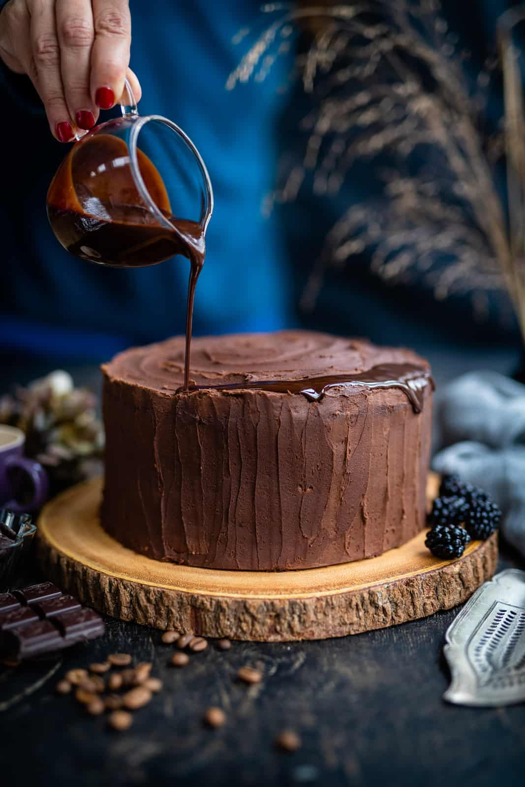 Adding a chocolate drip on a frosted chocolate cake