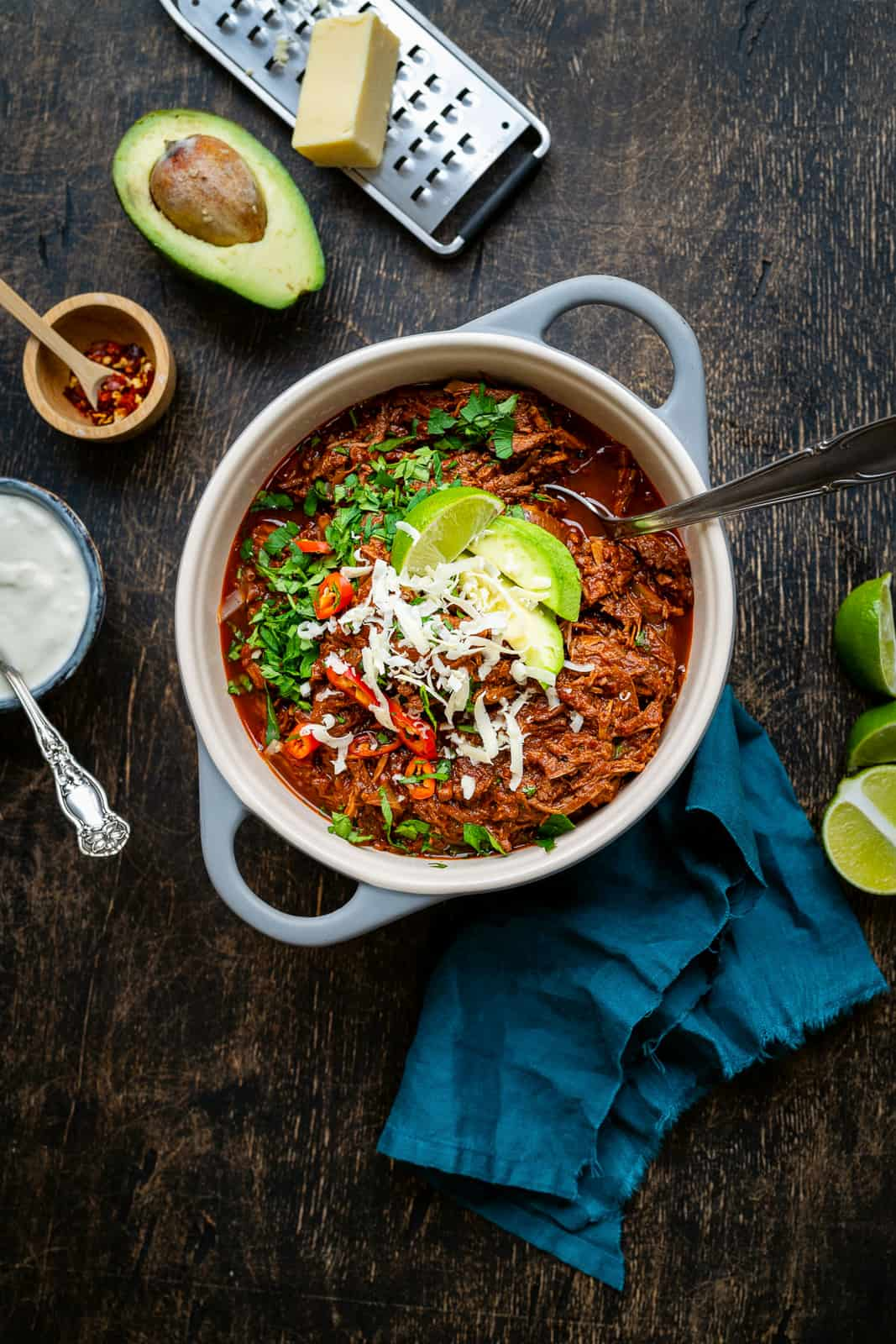 Pot of chunky beef chili topped with avocado, shredded cheese and cilantro