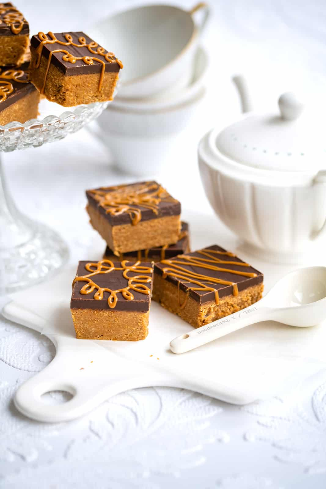 Biscoff Cookie bars on a ceramic white board with tea set on the side