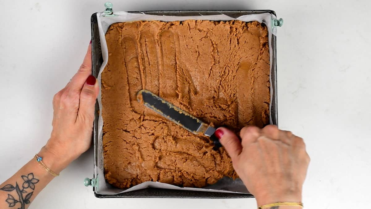 levelling cookie butter bar mix in a square lined tin