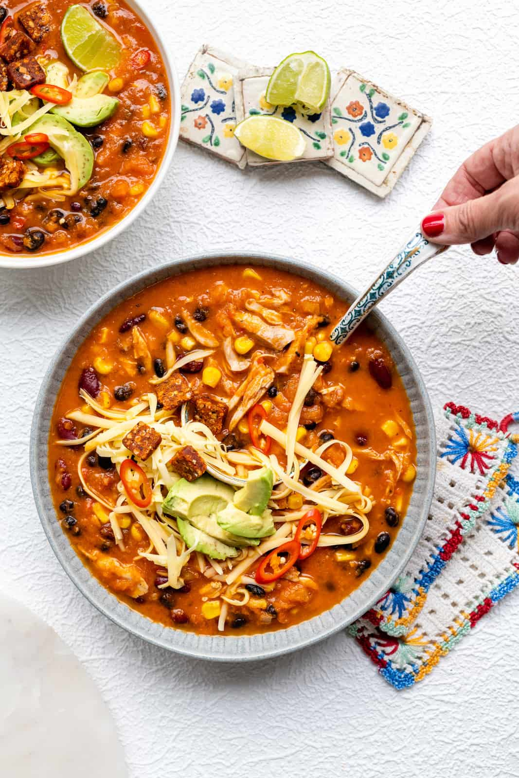 Bowl of creamy enchilada soup with corn, beans, chicken and toppings