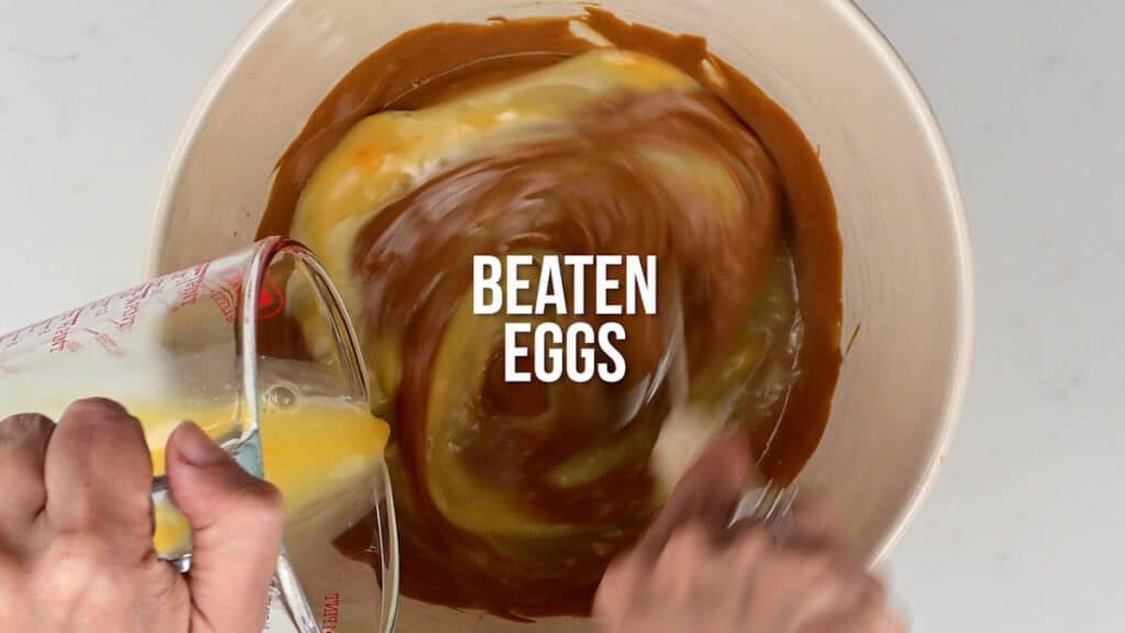 Mixing eggs into Biscoff muffin batter